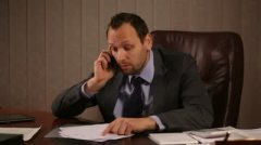 stock-footage-angry-boss-talking-on-the-phone-in-office